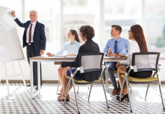 Smiling senior businessman conducting presentation in front of coworkers. Aged financial manager explaining new strategy to colleagues. Business presentation concept