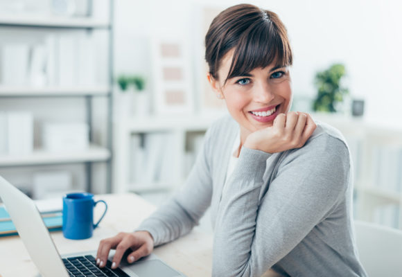 Happy confident businesswoman sitting at office desk and working with a laptop, she is smiling at camera
